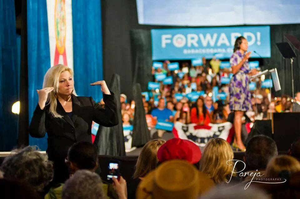 Shonna Magee Hudson signing during a speech by Michelle Obama
